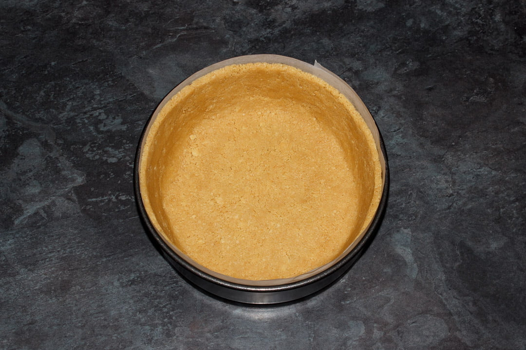 Biscuit crumbs pressed into the base and sides of a lined springform pan