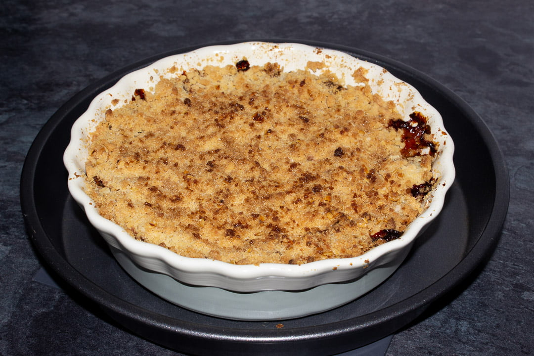 Baked apple crumble in a dish set on a baking tray