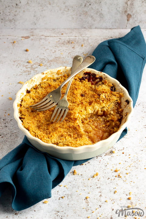 Apple crumble in a dish with two forks rested on top set over a blue linen napkin.