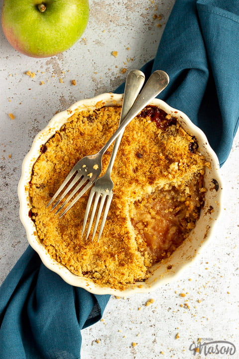 Apple crumble in a dish with two forks rested on top set over a blue linen napkin with a cooking apple in the background.