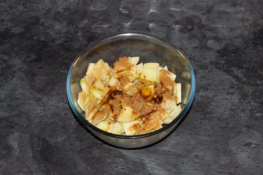 Sliced apples in a glass bowl with sugar, vanilla, cinnamon and water