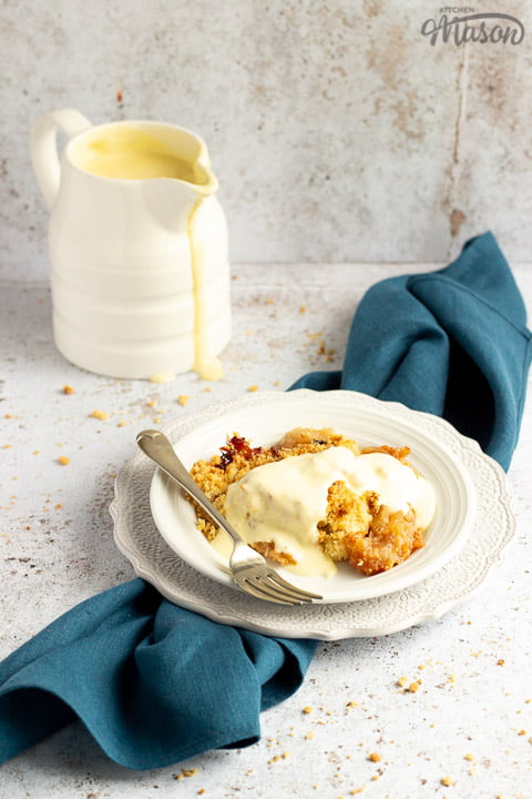 Slice of apple crumble in a small white bowl with a fork, drizzled with custard. There's a white jug of custard in the background and a blue linen napkin under the bowl.