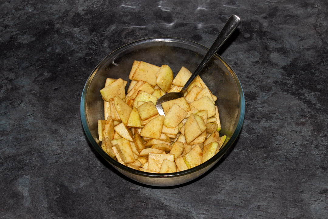 Sliced apples in a glass bowl with sugar, vanilla, cinnamon and water all mixed together