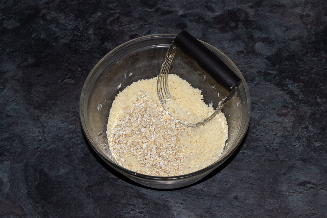 Crumble mixture with oats in a glass bowl with a pastry blender