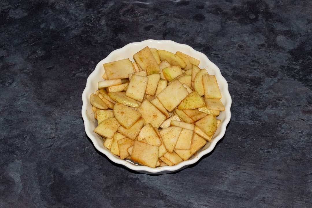 Sliced marinated apples in a dish