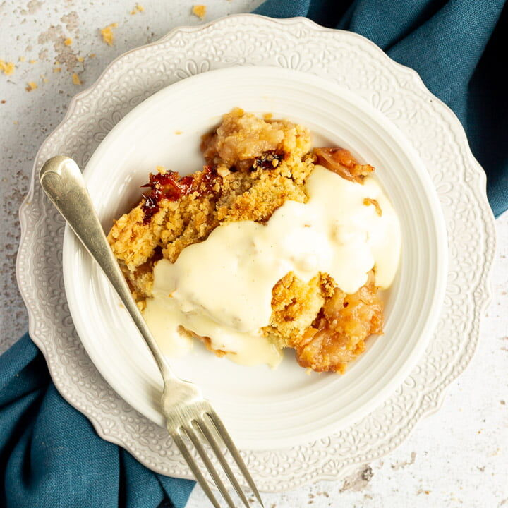 Slice of apple crumble in a small white bowl with a fork, drizzled with custard, set over a blue linen napkin.