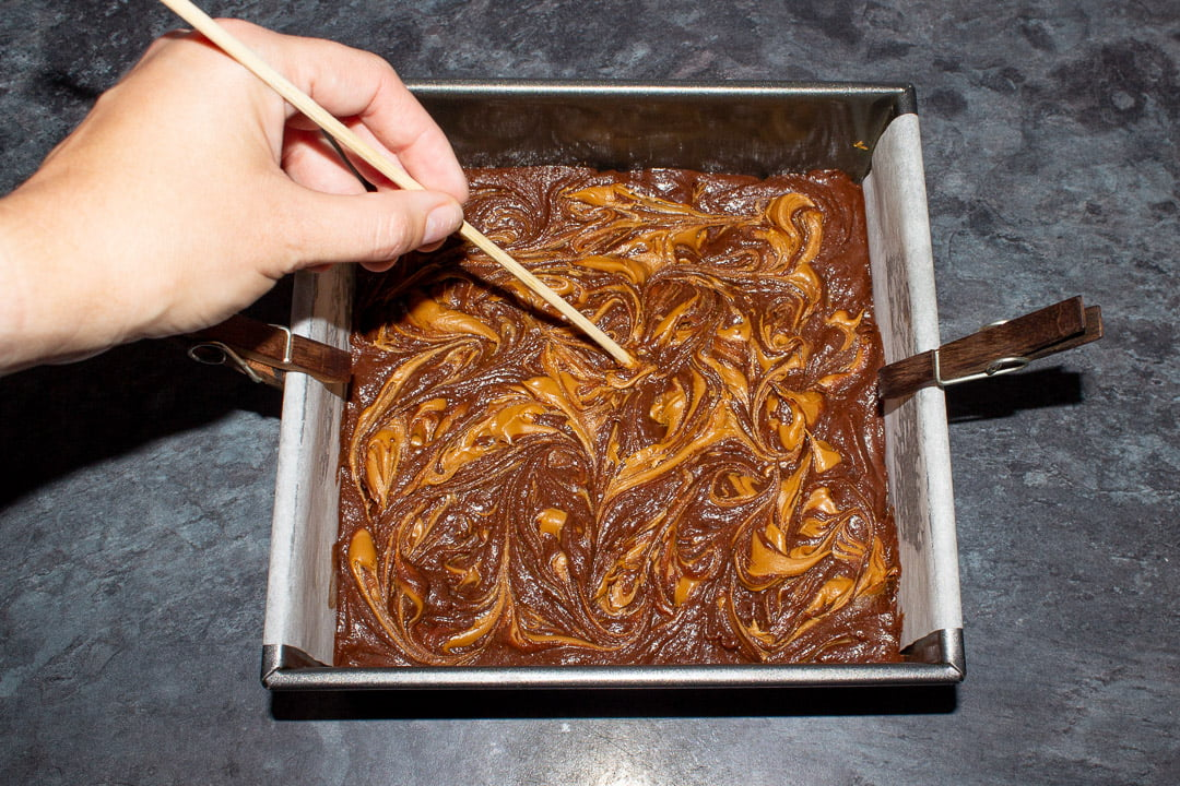 Biscoff spread being swirled into brownie batter with a skewer in a lined square baking tin