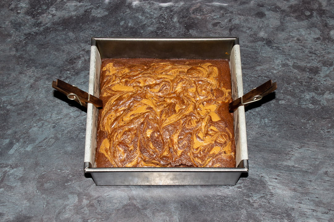 Baked Biscoff brownies in a lined square baking tin
