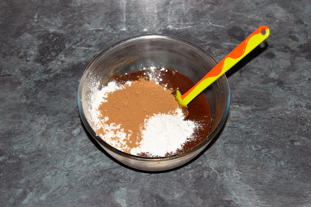 Melted dark chocolate, butter, eggs, sugar, vanilla, salt, cocoa powder and flour in a glass bowl with a rubber spatula