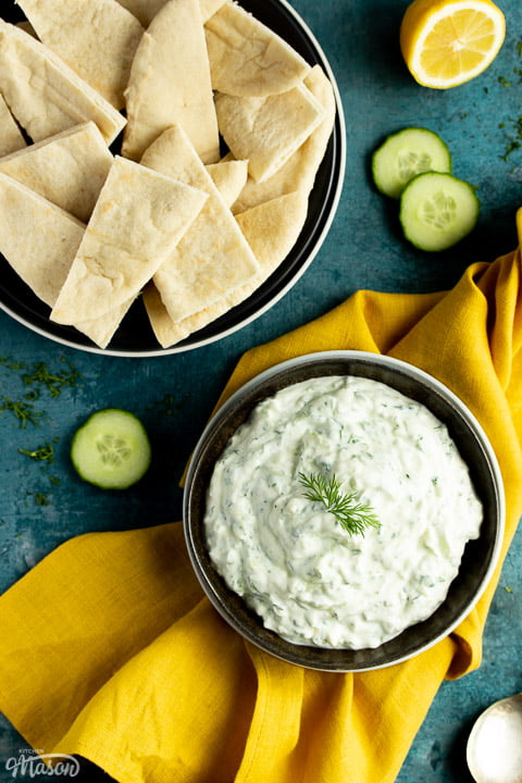 A bowl of tzatziki on a mustard yellow linen napkin with cucumber slices, half a lemon and pitta bread in the background