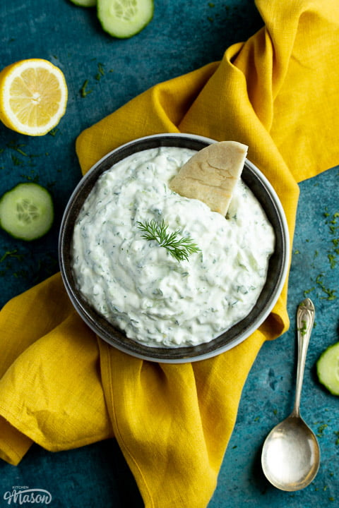 A bowl of tzatziki with pitta bread dipped in it on a mustard yellow linen napkin with cucumber slices, half a lemon and a spoon in the background