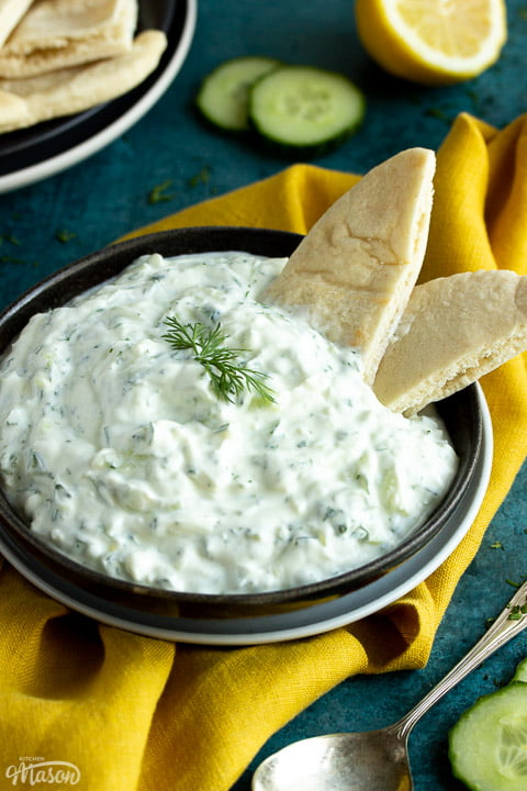 Close up of a bowl of tzatziki with pitta bread dipped in it on a mustard yellow linen napkin with cucumber slices, half a lemon and a spoon in the background