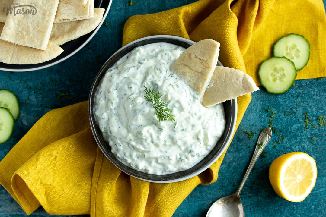 A bowl of tzatziki with pitta bread dipped in it on a mustard yellow linen napkin with cucumber slices, half a lemon, pitta bread and a spoon in the background