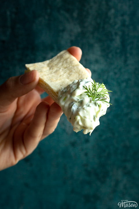 Close up of someone holding a pitta bread with a large dollop of tzatziki and a spring of fresh dill on the end