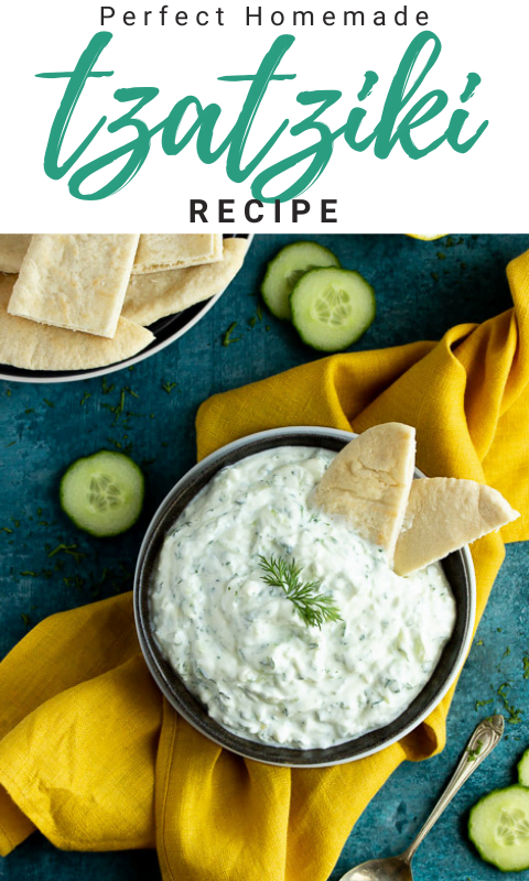 A bowl of tzatziki on a mustard yellow linen napkin with cucumber slices, pitta bread and a spoon in the background