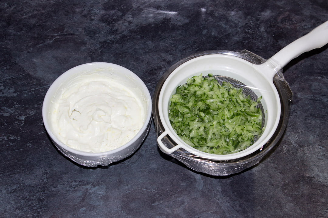Grated cucumber in a sieve set over a metal bowl covered in cling film and the remaining tzatziki dip ingredients (minus the dill) mixed together in a small white bowl also covered in cling film.