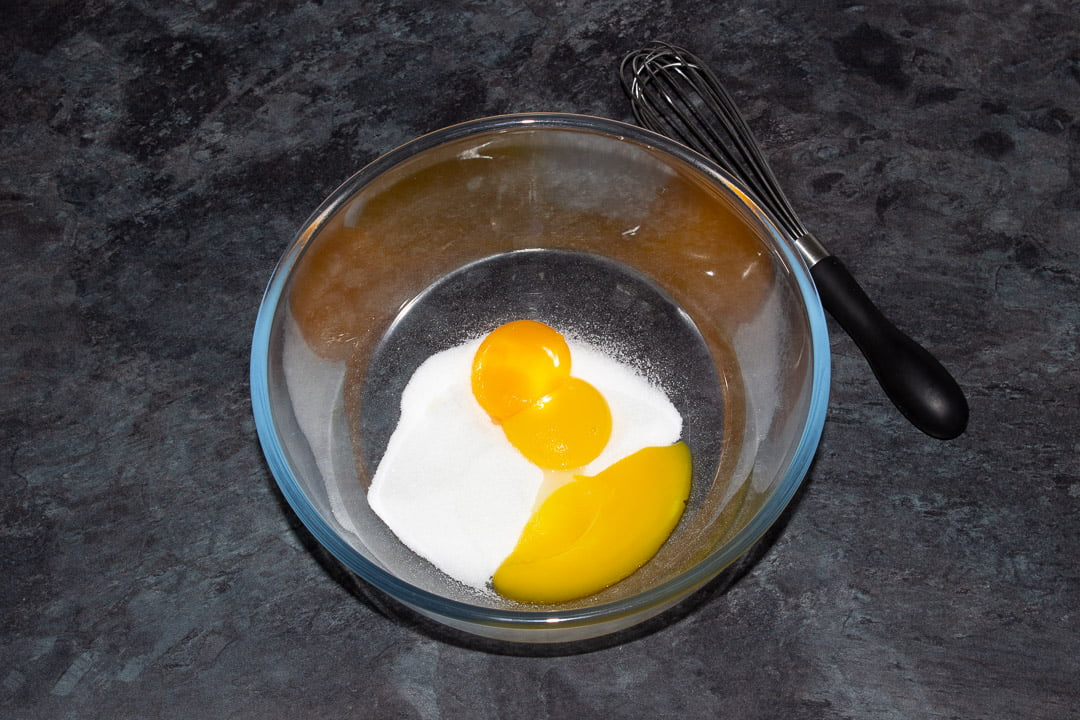 Egg yolks and sugar in a glass bowl