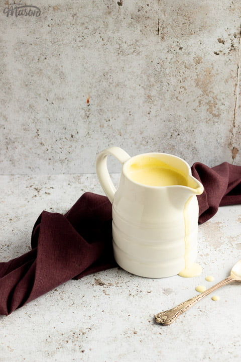 Homemade custard in a white jug on a burgundy linen napkin with drips running down the front and a silver spoon in the background