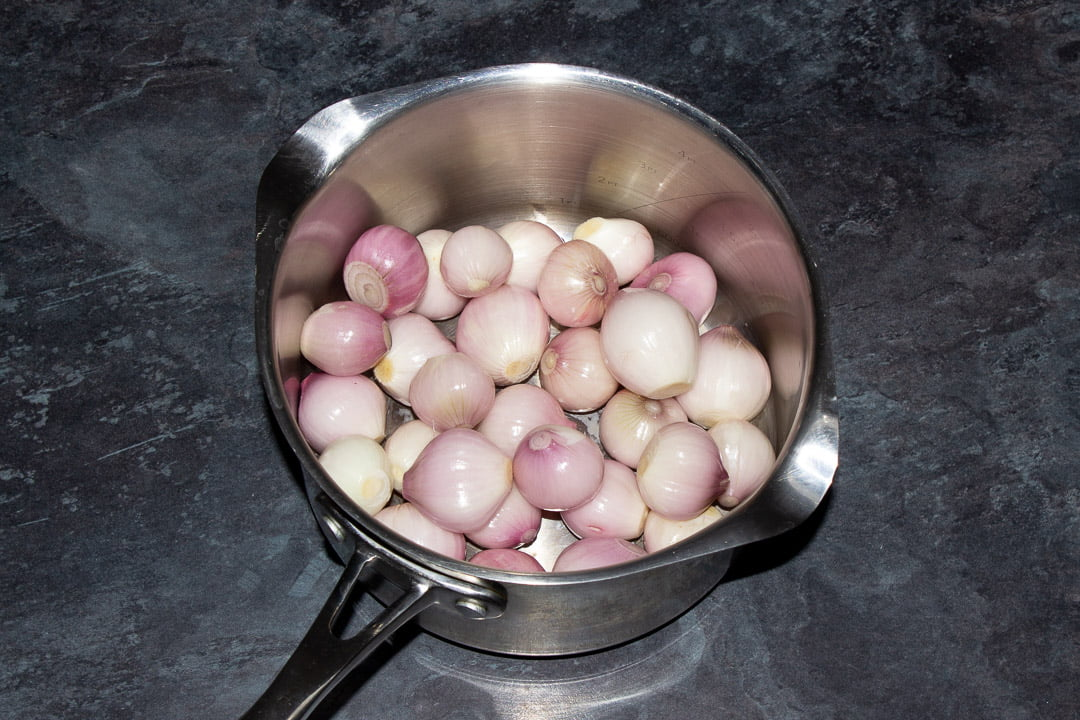 Peeled and trimmed baby shallots in a large saucepan