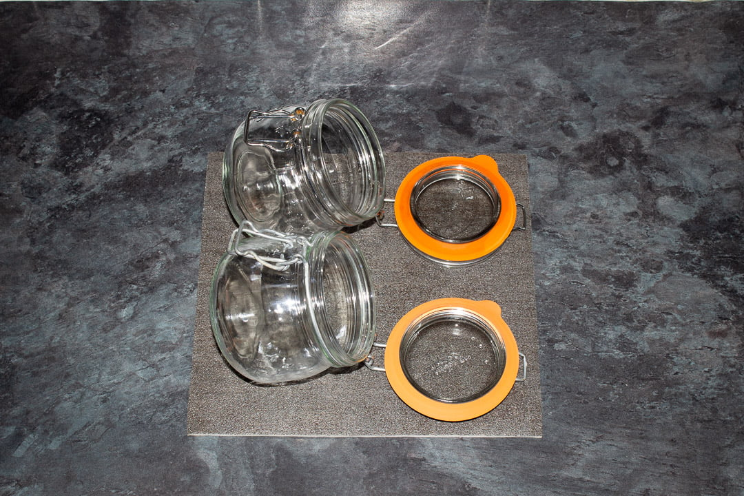 Two hot jars on a heat proof mat with the seals on