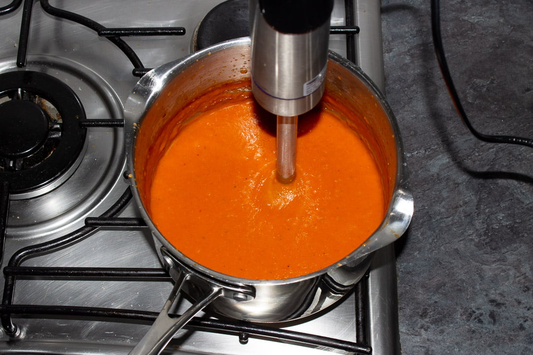 Tomato soup in a saucepan being blitzed with a stick blender