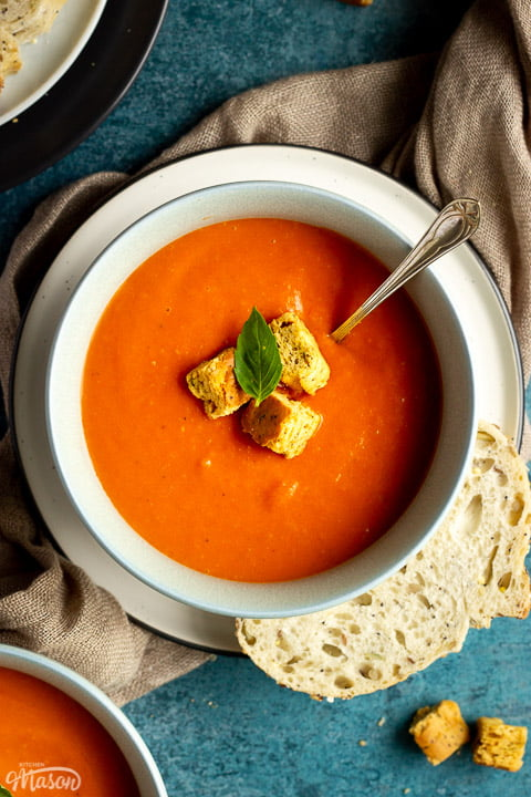 A bowl of tomato soup with croutons, a leaf of basil and a spoon inside, set on a plate on a light brown napkin with a slice of sourdough bread on the side. There is another bowl of soup, a plate with slices of bread and some croutons in the background.