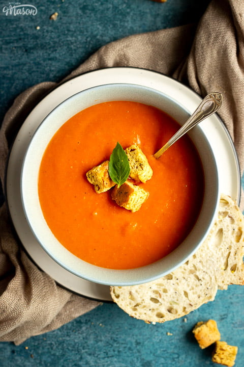 A bowl of tomato soup with croutons, a leaf of basil and a spoon inside, set on a plate on a light brown napkin with a slice of sourdough bread on the side. There are also some croutons in the background.