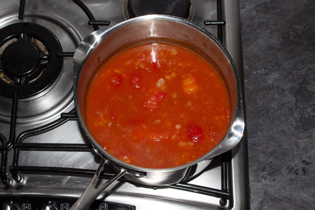 Tomato soup ingredients in a saucepan on a hob