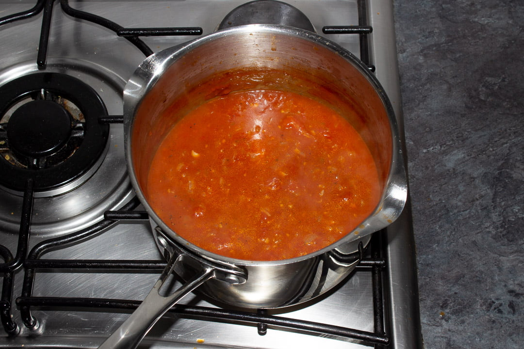 Reduced tomato soup in a saucepan on a hob