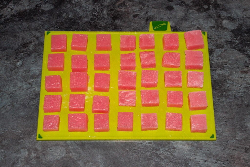 Turkish delight cut into cubes resting on a green chopping board