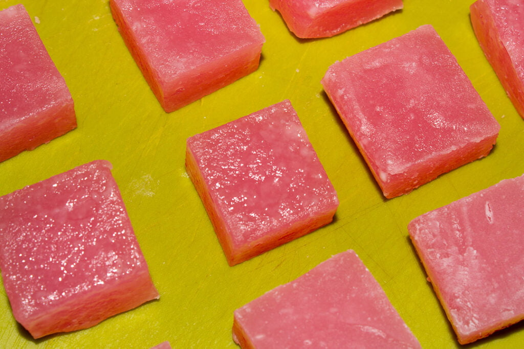 Sweating Turkish delight cut into cubes resting on a green chopping board