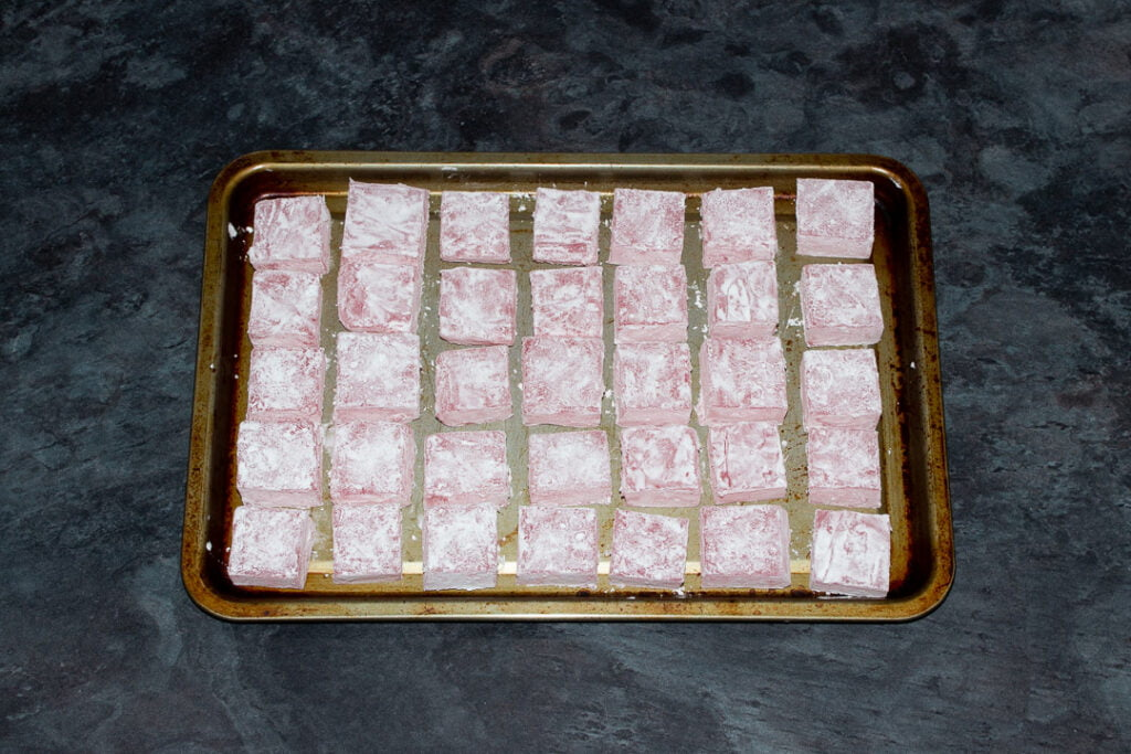 Turkish delight cubes coated in cornflour on a baking tray