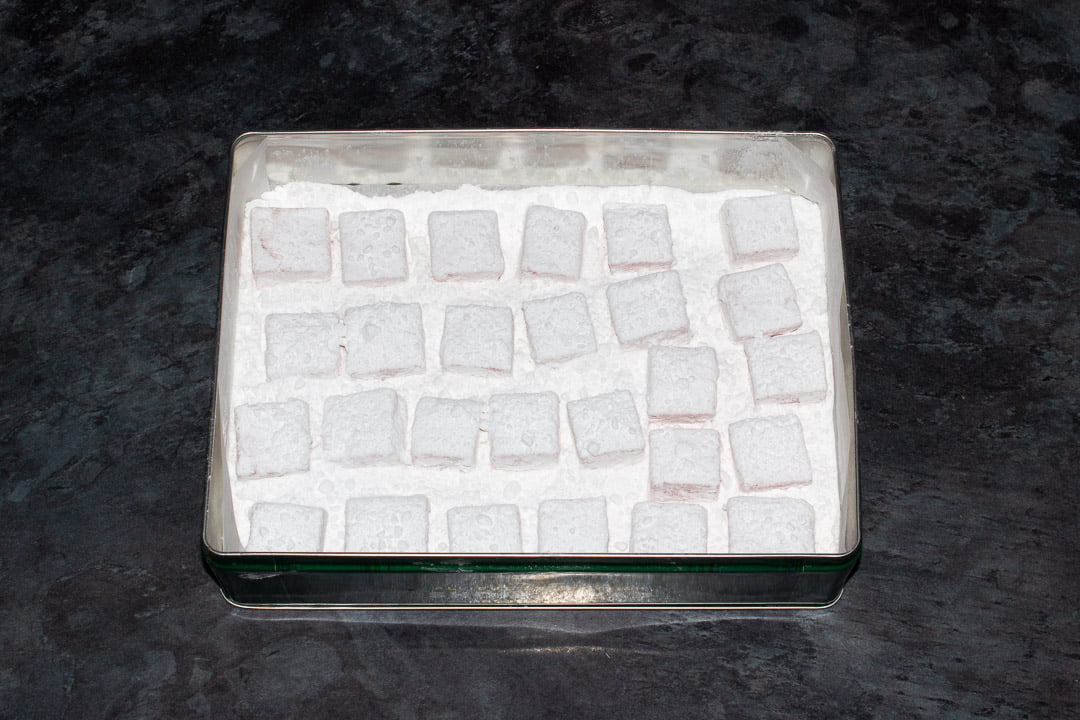 Cubes of Turkish delight in a metal tin filled with plenty of icing sugar