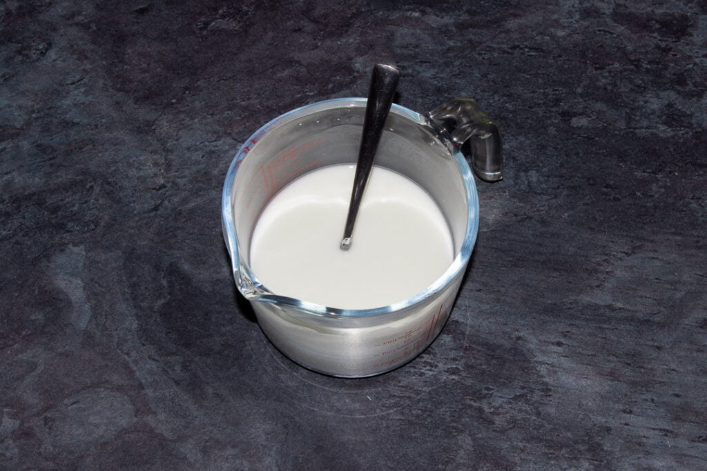 Cornflour dissolved in water in a glass jug with a metal teaspoon