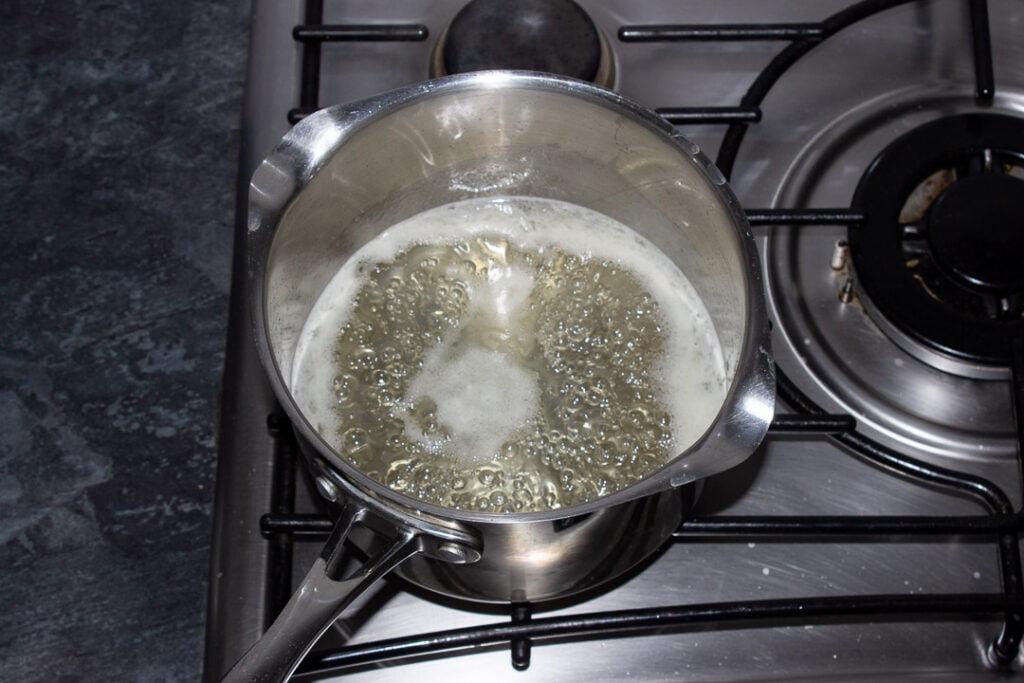 Sugar, lemon juice and water simmering in a saucepan on the hob