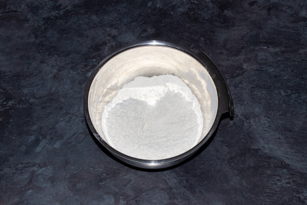 Flour, bicarbonate of soda, baking powder and salt in a small metal bowl on a kitchen worktop