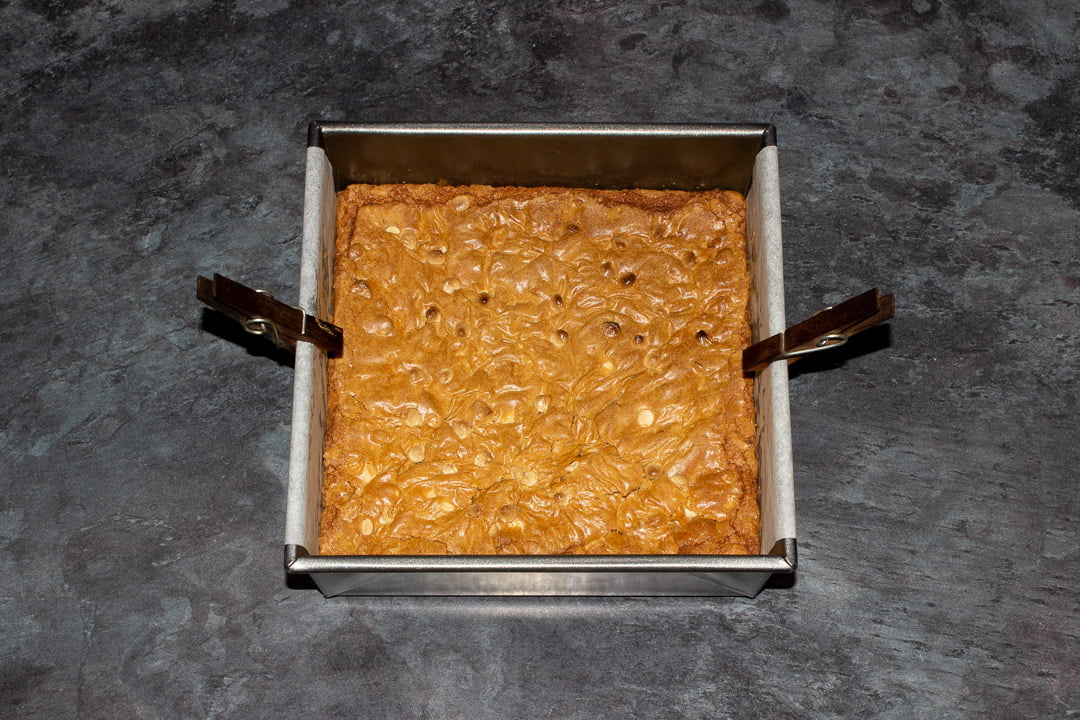 Baked white chocolate Biscoff blondies in a lined square baking tin