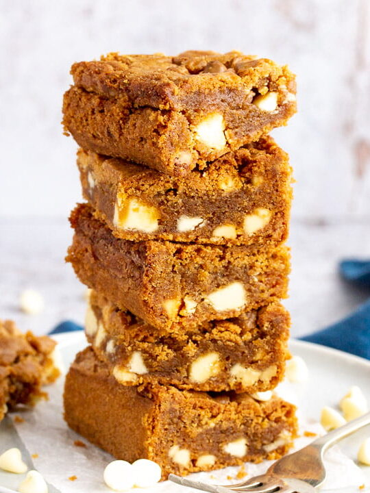 5 White chocolate Biscoff blondies in a stack on top of two plates with a fork on the side. An open jar of Biscoff spread with a spoon in it sits in the background and a blue linen napkin.