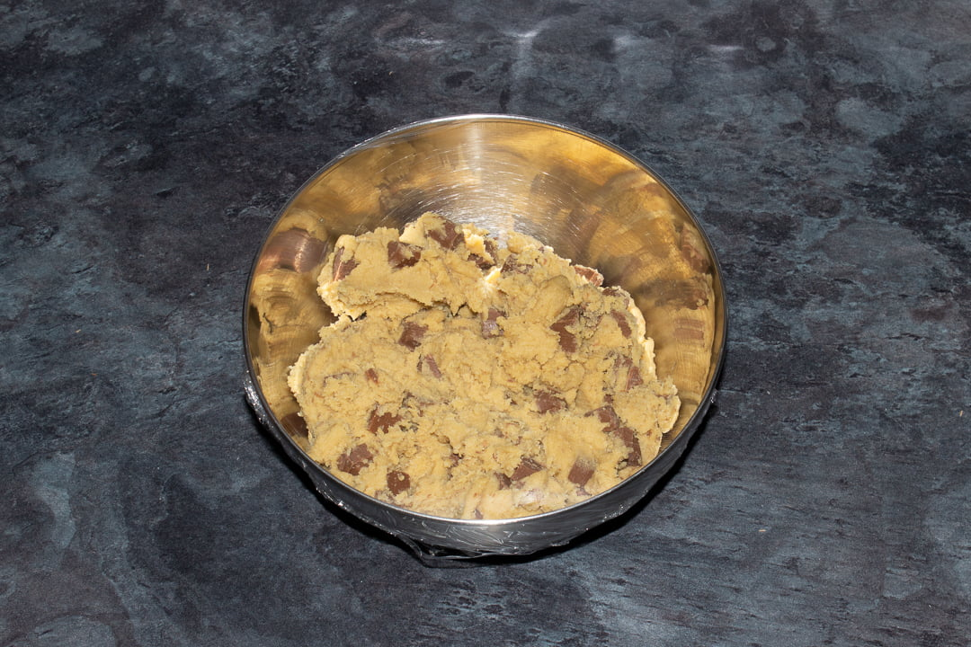 Chocolate chip cookie dough in a metal bowl covered with cling film