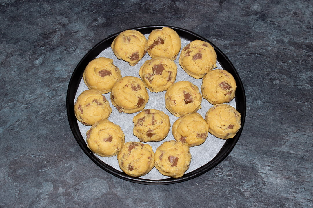 Balls of chocolate chip cookie dough on a black plate lined with baking paper
