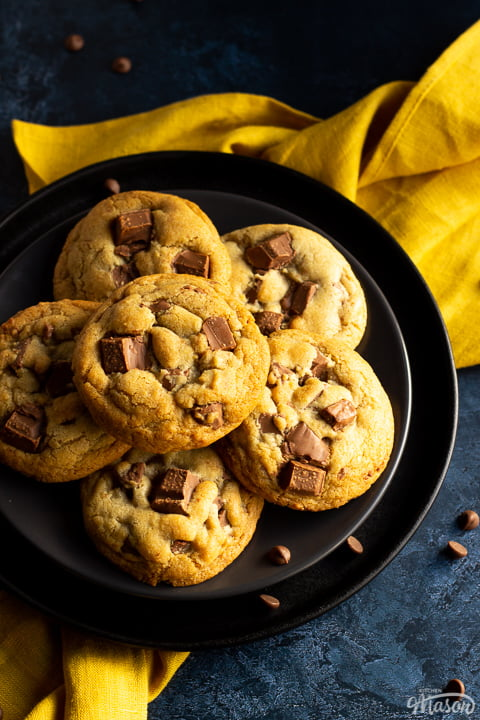 6 Chewy chocolate chip cookies on 2 stacked black plates set over a yellow linen napkin. With a deep blue marbled backdrop and chocolate chips scattered around.