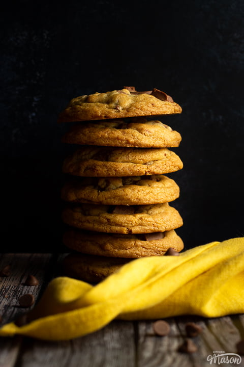 A stack of 7 chewy chocolate chip cookies against a deep blue marbled backdrop. There is a yellow linen napkin and chocolate chips scattered around it.