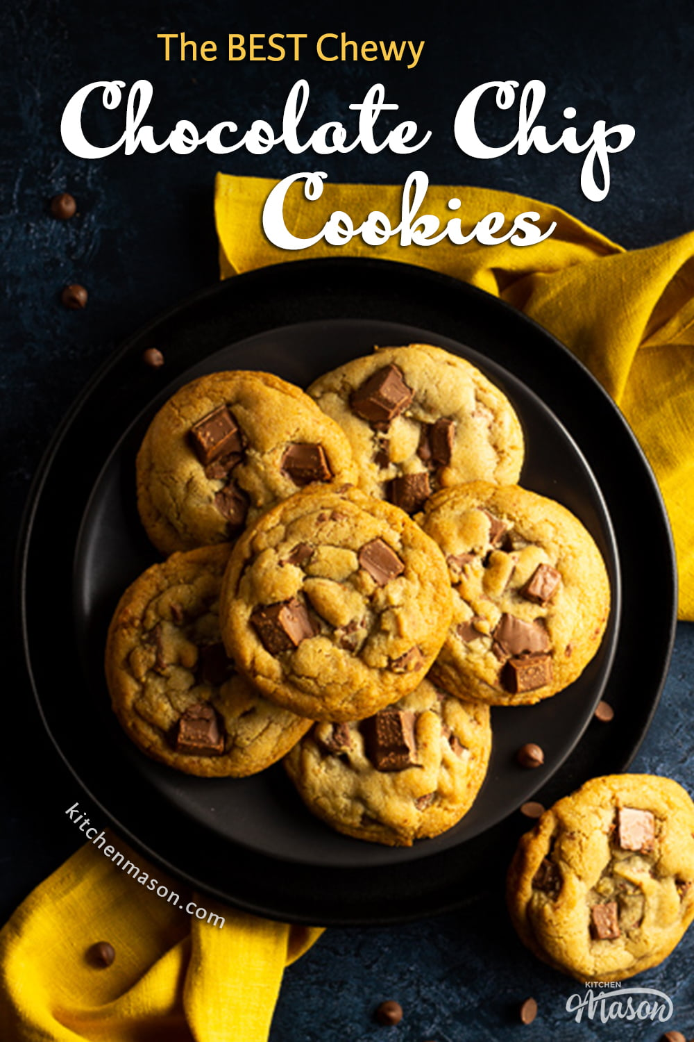 6 Chewy chocolate chip cookies on 2 stacked black plates set over a yellow linen napkin. With a deep blue marbled backdrop with more cookies and chocolate chips scattered around.