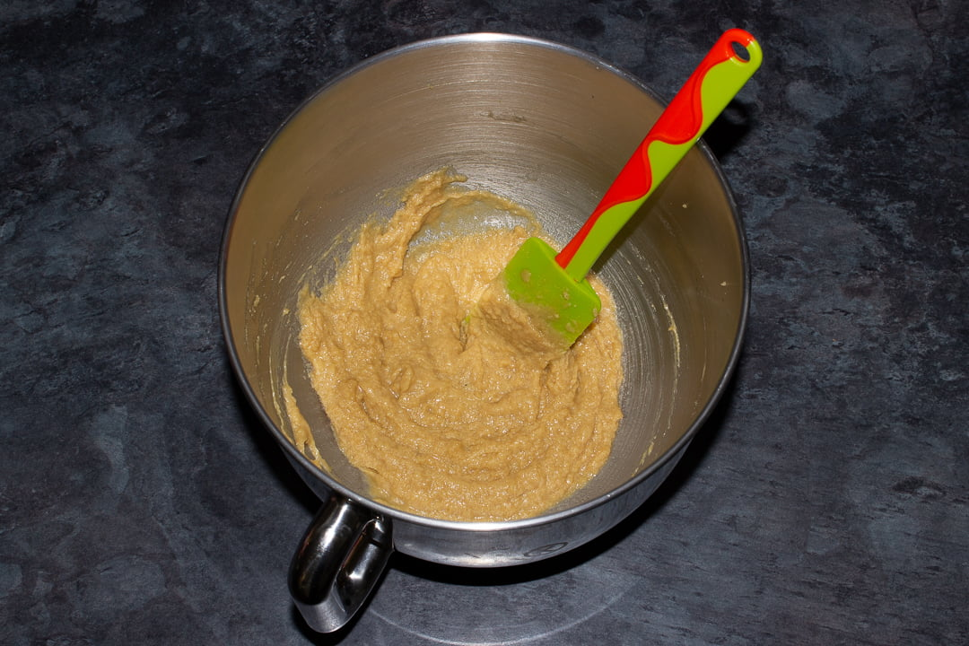 Creamed butter and sugar beaten with egg and vanilla in the bowl of an electric stand mixer with a green rubber spatula