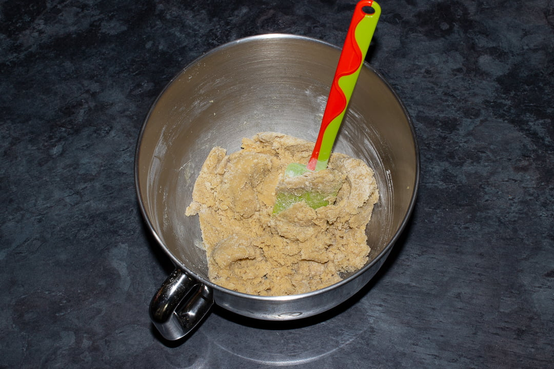 Cookie dough in the bowl of en electric stand mixer with a green rubber spatula