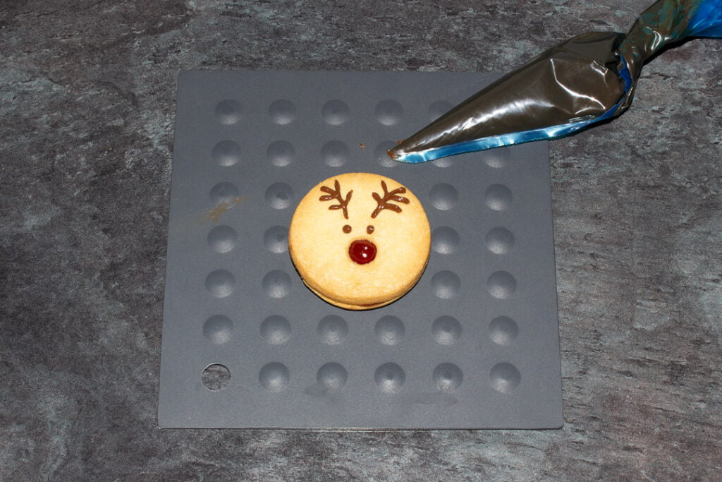 A reindeer cookie with the chocolate eyes and antlers piped on