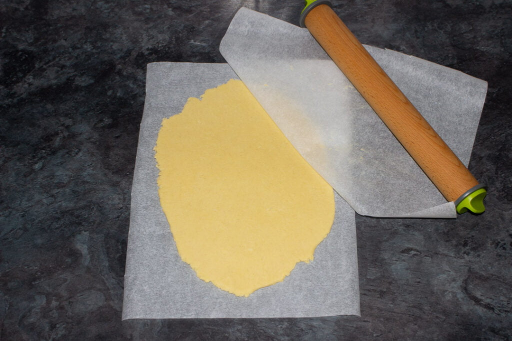 Cookie dough rolled out between two sheets of baking paper ready for cutting