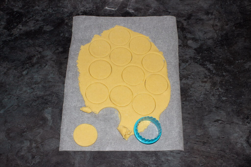 Cookie dough rolled out and cut on a sheet of baking paper with a small circular cookie cutter