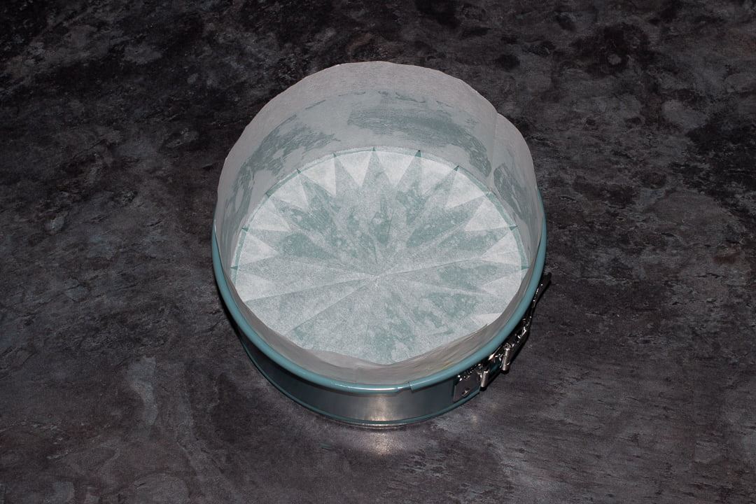 A springform baking tin greased and lined on the base and sides with baking paper