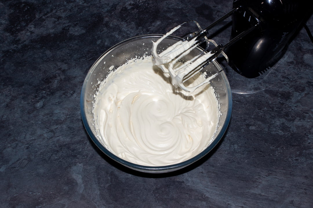 Baileys and double cream that's been whipped to stiff peaks in a glass bowl with an electric hand whisk